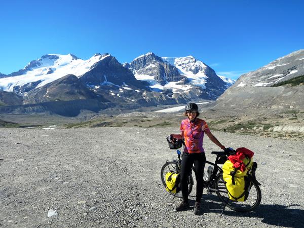 Cyclotouriste qui pose devant les Rocheuses Canadiennes